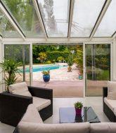 Veranda avec toiture en verre par jardin d'hiver dans veranda